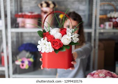 A bouquet of white and red roses in a red box in the outstretched hands of the girl florist.