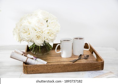 A bouquet of white roses in a round glass vase on a wooden tray a table with a two cups of tea and a wrapped rolled paper. Copy space
