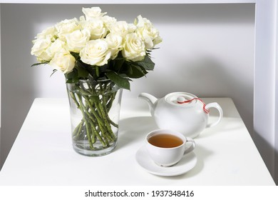 A bouquet of white roses in a vintage glass vase, a wooden tray with a cup of tea, a faience figurine of an angel. Greeting card for mother's day. Copy space