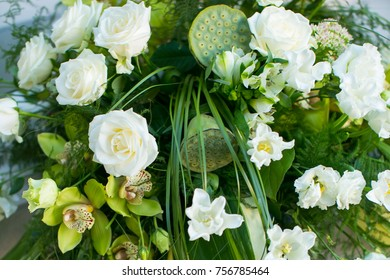 bouquet of white roses, yellow daffodils, greenery and lotuses