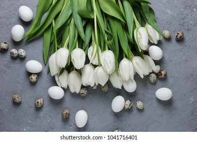 A bouquet of white tulips and chicken and quail eggs on a gray concrete background. Top view. Flat lay. Postcard for Easter and Spring Holidays