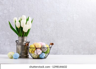 Bouquet of white tulips in silver can and wire basket with Easter eggs on the table. Postcard motif, copy space.