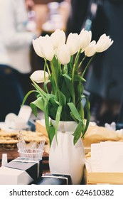Bouquet of white tulips in a vase on a table