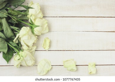 bouquet of white withered roses on a wooden table, vintage style, top view