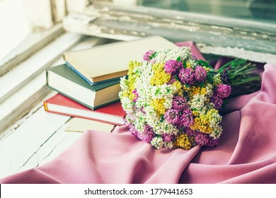 A bouquet of wild flowers and the books on the vintage windowsill.