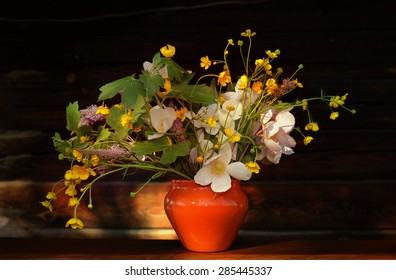 Bouquet of wild flowers on a wooden background in vintage style
