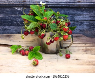 Bouquet of wild strawberries on rustic plywood background