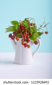 Bouquet of wild strawberries in teapot on blue  background