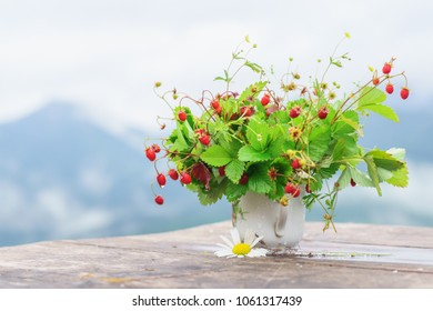 Bouquet of wild strawberry branches in a cup on a rustic wooden table with mountains on a background.
