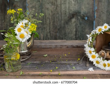 Bouquet of wild summer flowers in old vintage teapot over wooden background