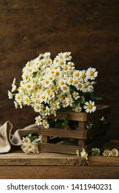 bouquet of wildflowers, chamomile on wooden background