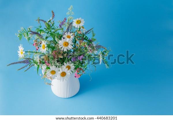 bouquet of wildflowers in jar on plain blue background