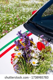 A bouquet of wildflowers on the hood of a car against a flowering meadow. Close-up. Vertical photograph.