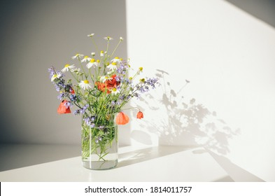 Bouquet of wildflowers in a small glass vase on the white table. Poppies, chamomiles, cornflowers, green grass. Summer photo. Contrast shadows on the white wall. Country style. - Shutterstock ID 1814011757