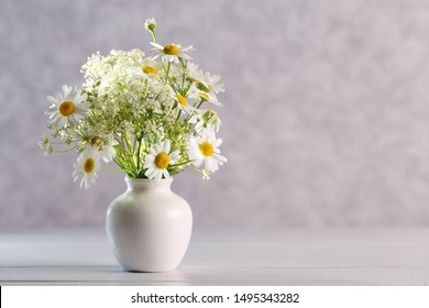 Bouquet of wildflowers in a white vase on a light background.