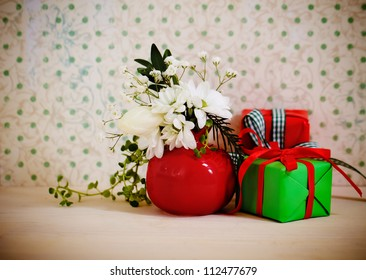 Bouquet of winter flowers with presents decorated with ribbon