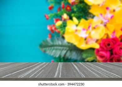 the bouquet of yellow artificial orchid made from fabric decorating on green wall (blur background and wooden table for displaying your product) - Shutterstock ID 394472230
