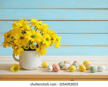 Bouquet of yellow chrysanthemum and colored Easter eggs over blue wooden background
