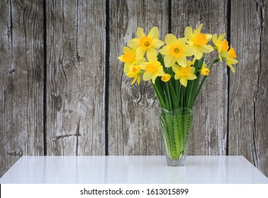 Bouquet of yellow daffodils in a glass vase on a white table on a background of old dirty wooden boards. Easter background