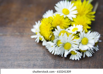 Bouquet of yellow dandelion and daisy flower in wooden desk.