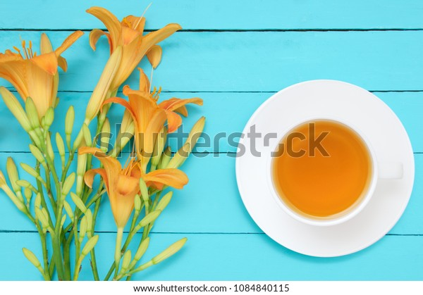 A bouquet of yellow flowers hemerocallis and a white cup on a saucer with green tea on a turquoise wooden background. View from above hemerocallis
