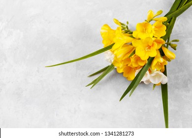 Bouquet of yellow freesias on grey stome background, copy space top view