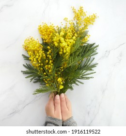a bouquet of yellow mimosa flowers on a marble background. Concept of women's or mothers day