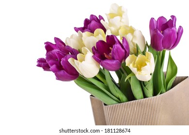 bouquet from yellow and purple tulips in brown  paper package isolated on white