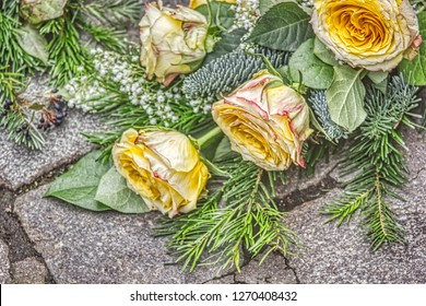 Bouquet of yellow roses in cretan design on gray paving stones.
