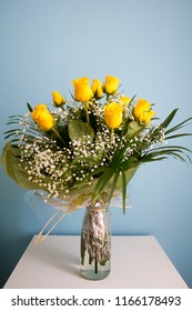 Bouquet of yellow roses on a smooth, white surface with a bluish background