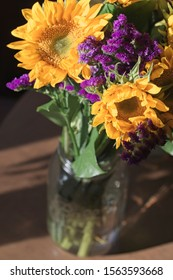 Bouquet of yellow sunflower and purple statice in a mason jar