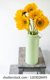 Bouquet of yellow sunflowers , flower in vase on old vintage table. Room morning. Gray background. Colors of autumn and mood fall