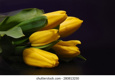 Bouquet of yellow tulips on a black background