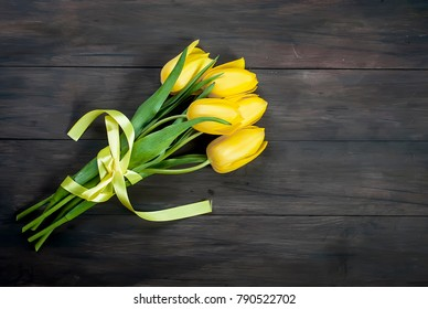 bouquet of yellow tulips with yellow ribbon on vintage dark wooden table background.  holidays concept. Copy space.