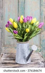 Bouquet of yellow and violet tulips in silver watering can