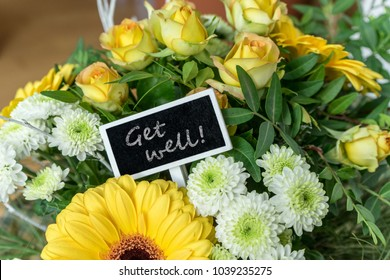 Bouquet of yellow and white roses, gerberas, chrysanthemums and a small board with English text: get well soon