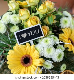 Bouquet of yellow and white roses, gerberas, chrysanthemums and a small chalkboard with text: I love you
