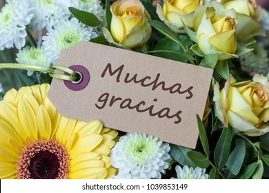 Bouquet of yellow and white roses, gerberas, chrysanthemums and greeting card with spanish text: Thank you