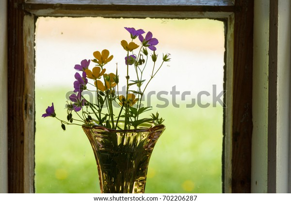 Bouquets, floristry concept. Closeup composition of flowers in glass vase standing in front of window
