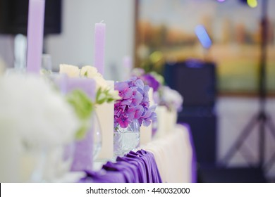 Bouquets of lilac stand on the festive dinner table