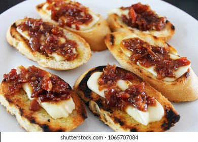 Bourbon bacon jam and brie crostini. Six crostini on a white plate.