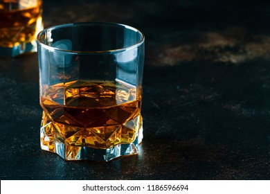 Bourbon in glass, american corn whiskey, dark bar counter, selective focus