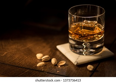 Bourbon Whisky Scotch on Rock with Pistachios on Marble Coaster Bubble Rock Glass