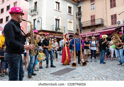 BOURG-SAINT-MAURICE, FRANCE - AUGUST 19, 2018: Brass band and Alphorn players play music, entertaining tourists and local people during traditional Agricultural and Mountain Fair at Savoie region.