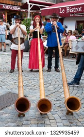 BOURG-SAINT-MAURICE, FRANCE - AUGUST 19, 2018: Musicians play alphorn, entertaining tourists and local people during traditional Agricultural and Mountain Fair market at Savoie region.