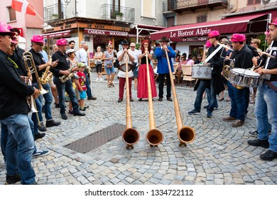 BOURG-SAINT-MAURICE, FRANCE - AUGUST 19, 2018: Alphorn players and brass band play music, entertaining tourists and local people during traditional Agricultural and Mountain Fair at Savoie region.