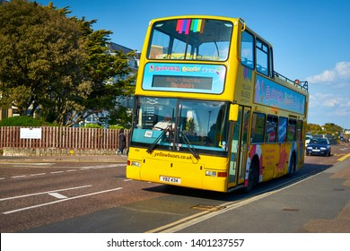 Bournemouth, Dorset / England - May 11 2019: Double Decker Open Topper  Bournemouth Yellow Busters Beach Bus towards Sandbanks via Dorset Coast. Famous Dorset UK, Tourist Attraction.
