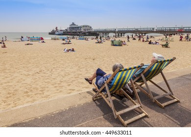 Bournemouth, Dorset, England, UK: 26 April 2011 - Senior couple sitting in deckchairs overlooking Bournemouth beach and pier, Dorset, England.
