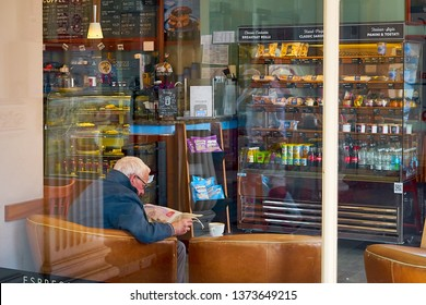 Bournemouth, Dorset / UK - April 8 2019:  Relaxing day in coastal town. Candid photography of older man drinking coffee and reading newspaper in Caffe Nero in Boscombe, Royal Arcade Shopping Centre.