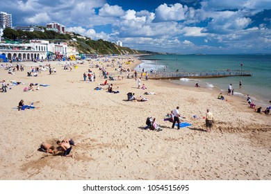 Bournemouth, Dorset, UK - August 29, 2006: Families relaxing on a sandy beach on a summer day in Bournemouth